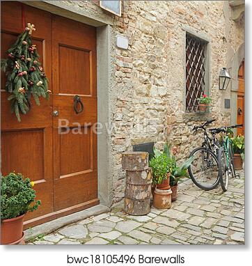 Art Print of Doorway to the tuscan house with christmas wreath and parked bicycles in village Montefioralle near Greve in Chianti Italy & Doorway to the tuscan house with christmas wreath and parked bicycles in village Montefioralle near Greve in Chianti Italy art print poster