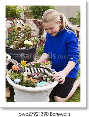 Young girl helping to make fairy garden in a flower pot art print poster