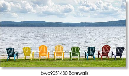 Eight colorful Adirondack chairs lined up on the beach looking out on the  lake, mountains and clouds. art print poster
