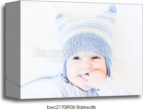 4bf45a4499bbd Canvas Print of Little baby in a funny blue hat on white background ...