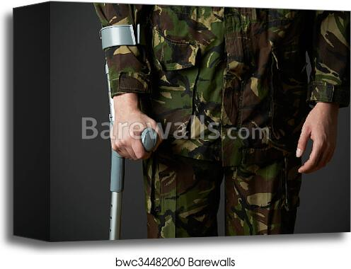 canvas print of studio shot of wounded soldier using crutch
