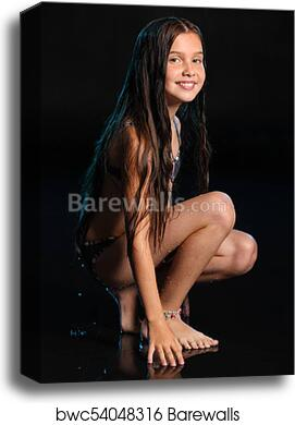 Canvas Print Of Slender Pre Teen Girl Smiles And Squats Barefoot In A Bikini