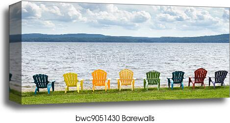 Eight colorful Adirondack chairs lined up on the beach looking out on the  lake, mountains and clouds. canvas print
